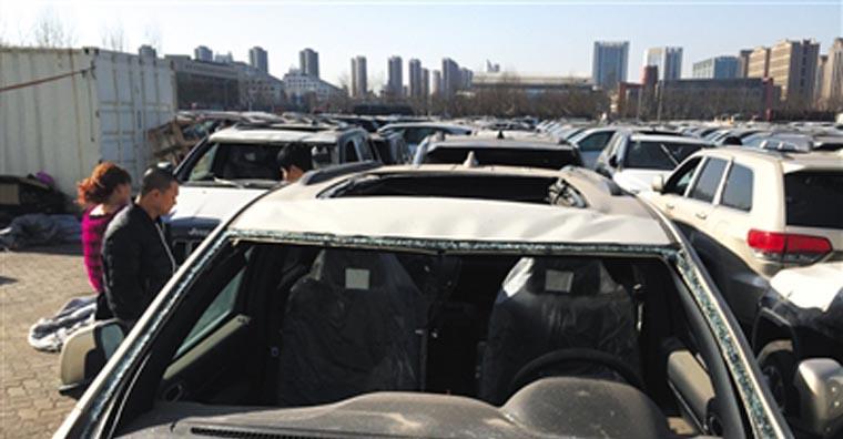 """25日,天津""""中电物流""""停车场,购车者正在参观天津港爆炸受损车辆"""